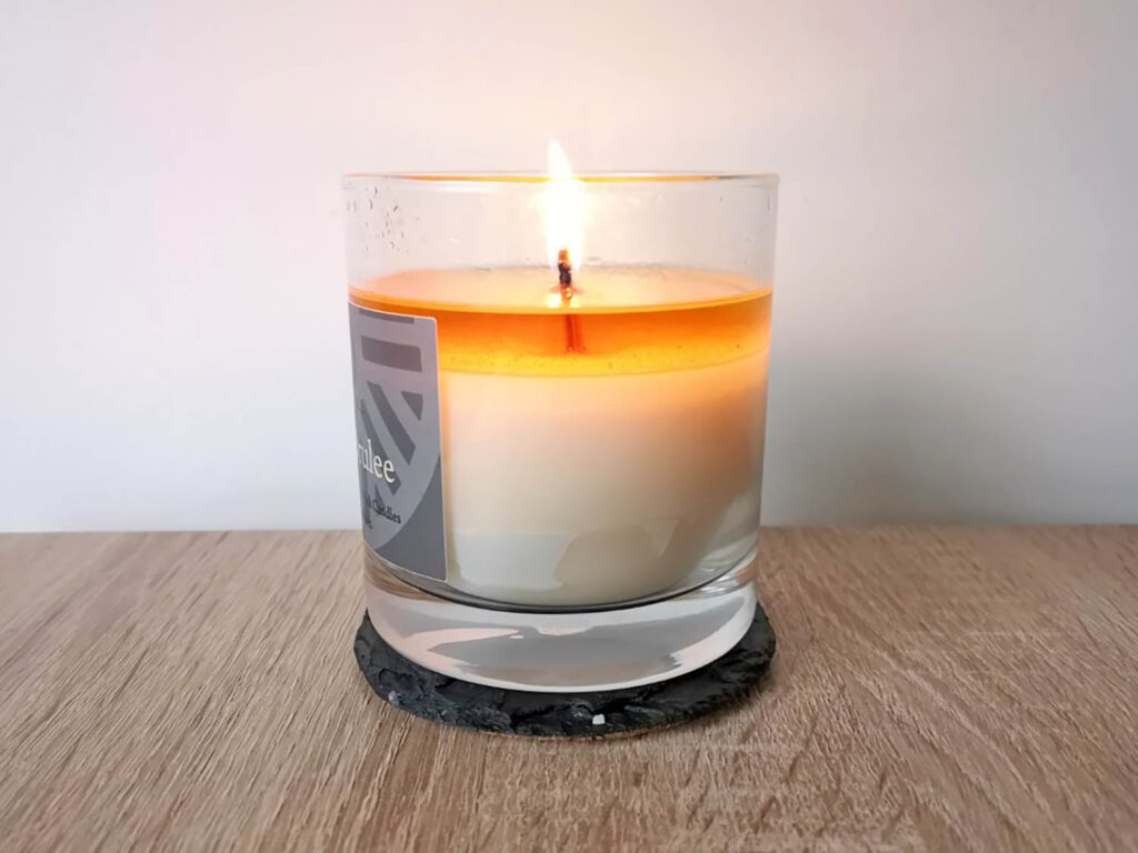 A Valley Mill wood wick candle with a full melt pool